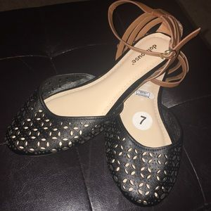 Black flats with brown ankle strap.
